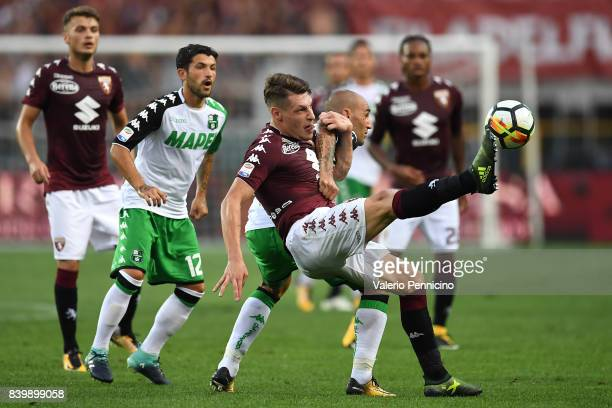 Andrea Belotti of Torino FC is challenged by Paolo Cannavaro of US Sassuolo during the Serie A match between Torino FC and US Sassuolo FC at Stadio...