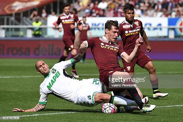 Andrea Belotti of Torino FC is tackled by Paolo Cannavaro of US Sassuolo Calcio during the Serie A match between Torino FC and US Sassuolo Calcio at...