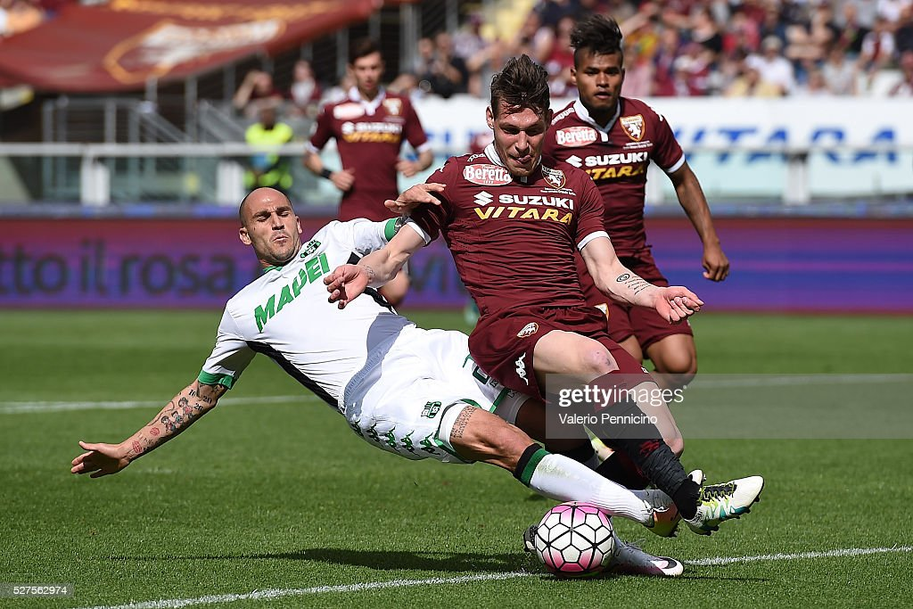 Andrea Belotti (R) of Torino FC is tackled by Paolo Cannavaro of US Sassuolo Calcio during the Serie A match between Torino FC and US Sassuolo Calcio at Stadio Olimpico Grande Torino on April 24, 2016 in Turin, Italy.