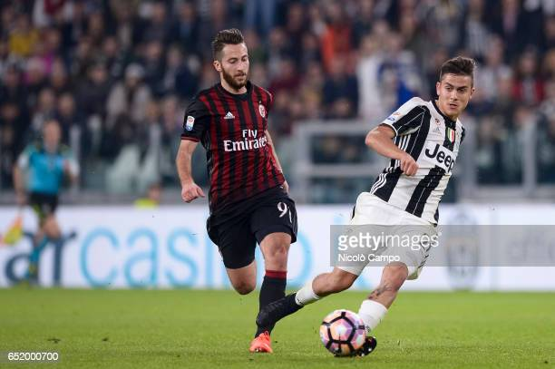 Andrea Bertolacci of AC Milan and Paulo Dybala of Juventus FC compete for the ball during the Serie A football match between Juventus FC and AC Milan...