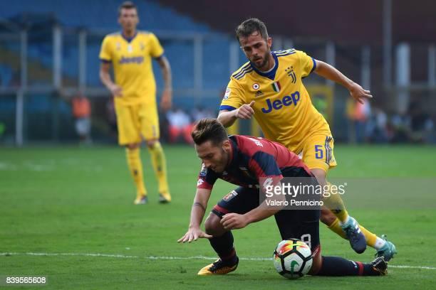 Andrea Bertolacci of Genoa CFC is tackled by Miralem Pjanic of Juventus during the Serie A match between Genoa CFC and Juventus at Stadio Luigi...