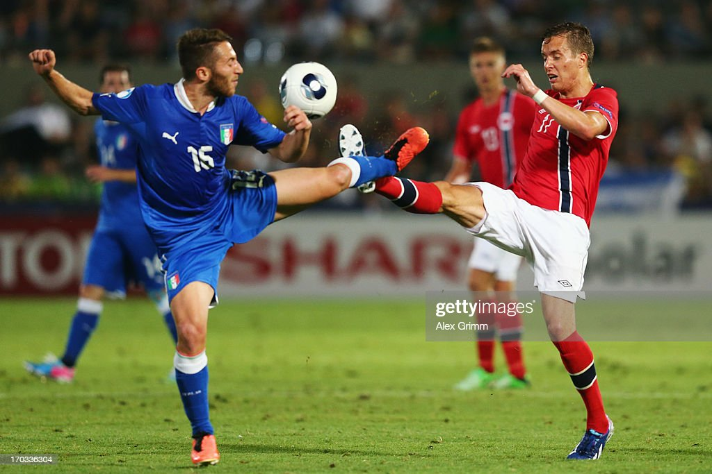 Andrea Bertolacci (L) of Italy is challenged by Anders Konradssen of Norway during the UEFA European U21 Championship Group A match between Norway and Italy at Bloomfield Stadium on June 11, 2013 in Tel Aviv, Israel.