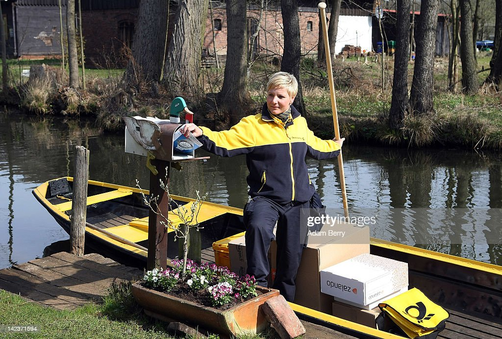 Andrea Bunar an employee of German postal carrier Deutsche Post DHL delivers mail to a house on the narrow canals in the Spreewald forest on her...