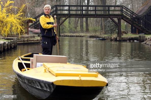 Andrea Bunar an employee of German postal carrier Deutsche Post DHL navigates her punt through the narrow canals in the Spreewald forest while...