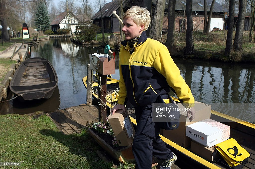 Andrea Bunar an employee of German postal carrier Deutsche Post DHL delivers a package to a house on the narrow canals in the Spreewald forest on her...