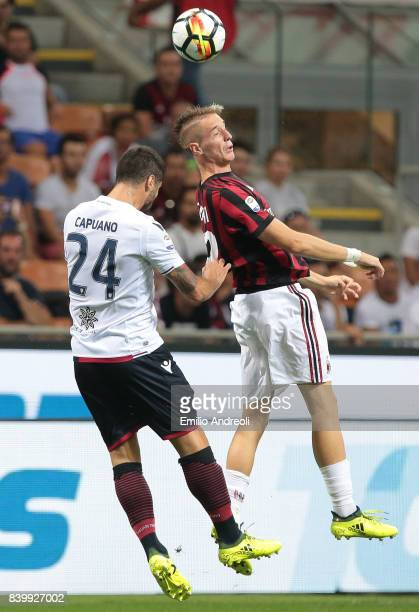 Andrea Conti of AC Milan jumps for the ball with Marco Capuano of Cagliari Calcio during the Serie A match between AC Milan and Cagliari Calcio at...