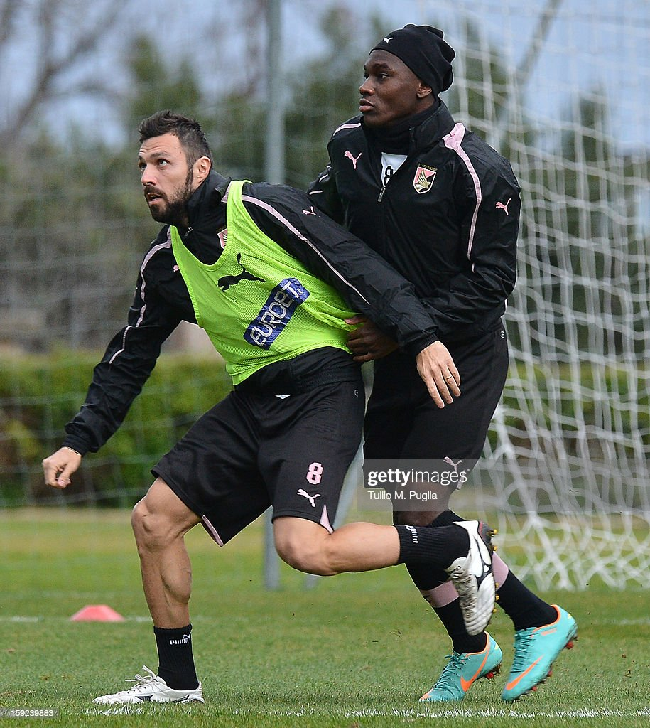 Andrea Dossena (L) of Palermo in action with his team-mate Cephas Malele during a training session at Tenente Carmelo Onorato Sports Center on January 10, 2013 in Palermo, Italy.