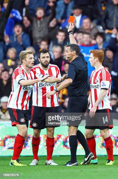 Andrea Dossena of Sunderland is sent off with a red card by referee Andre Marriner as teammate Sebastian Larsson protests during the Barclays Premier...