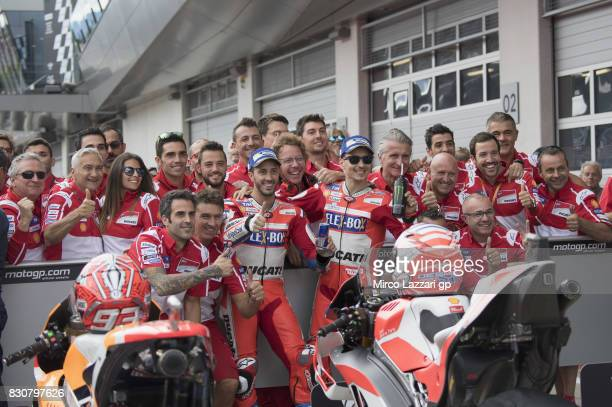Andrea Dovizioso of Italy and Ducati Team and Jorge Lorenzo of Spain and Ducati Team celebrate with team at the end of the qualifying practice during...