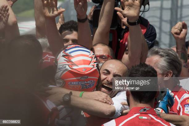 Andrea Dovizioso of Italy and Ducati Team celebrates the victory under the podium with Claudio Domenicali of Italy at the end of the MotoGP race...