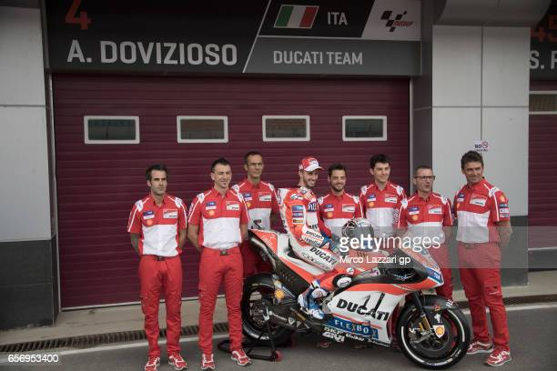 Andrea Dovizioso of Italy and Ducati Team poses with team on pit for the official photo during the MotoGp of Qatar Free Practice at Losail Circuit on...