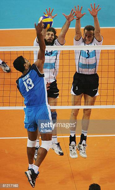 Andrea Giani of Italy spikes the ball against Alejandro Spajic and Gustavo Porporatto of Argentina competes in the men's indoor Volleyball...