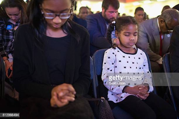 Andrea Kimpson and her sister Amanda listen to a prayer during a town hall meeting with Democratic presidential candidate Hillary Clinton at Royal...