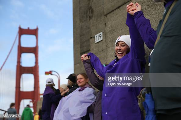 Andrea Mowrer smiles while linking hands with demonstrators across the Golden Gate Bridge on January 20 2017 in San Francisco California Organizers...