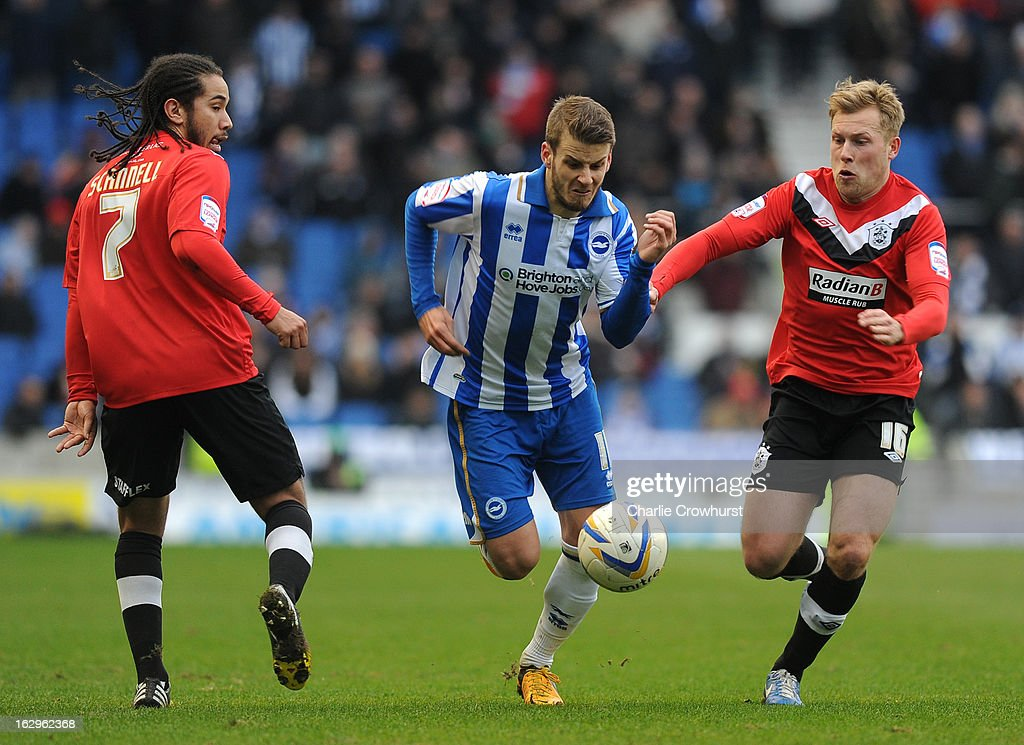 Andrea Orlandi of Brighton & Hove Albion breaks past Huddersfield pair Sean Scannell and Scott Arfield during the npower Championship match between Brighton & Hove Albion and Huddersfield Town at The Amex Stadium on March 02, 2013 in Brighton England.