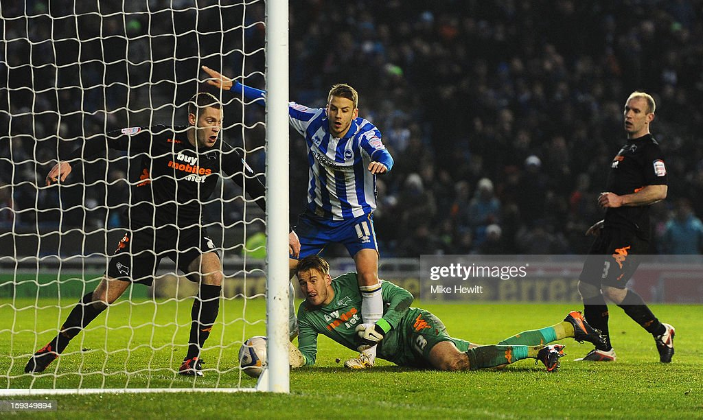Andrea Orlandi of Brighton is denied by Paul Coutts of Derby as goalkeeper Adam Legzdins and Gareth Roberts of Derby look on during the npower Championship match between Brighton & Hove Albion and Derby County at Amex Stadium on January 12, 2013 in Brighton, England.