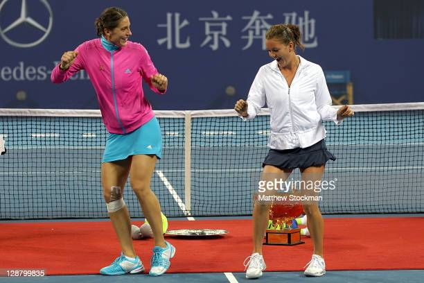 Andrea Petkovic of Germany instructs Agnieszka Radwanska of Poland on her victory dance during the trophy ceremony after the final of the China Open...
