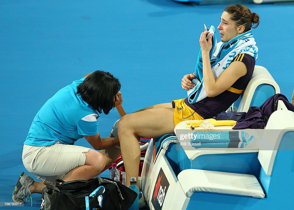 Andrea Petkovic of Germany is checked by a trainer after injurying her right knee in her group A singles match Ashleigh Barty of Australia during day one of the Hopman Cup at Perth Arena on December 29, 2012 in Perth, Australia.