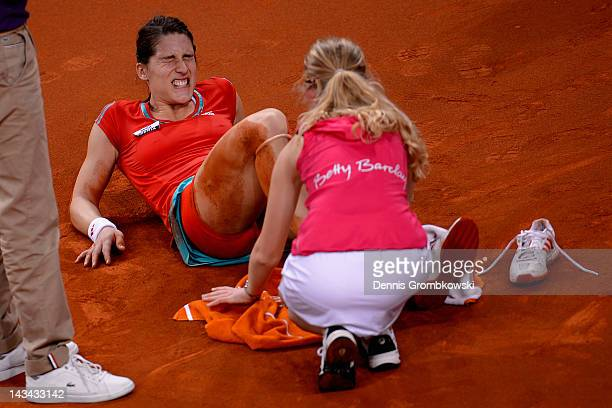 Andrea Petkovic of Germany sits on the court after suffering an injury in her match against Victoria Azarenka of Belarus during day four of the WTA...