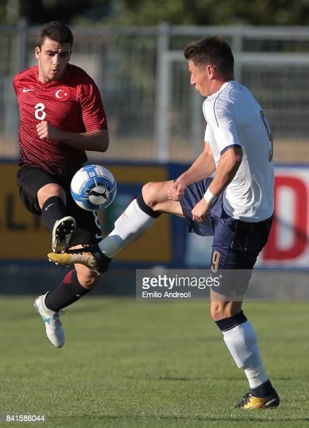 Andrea Pinamonti of Italy competes for the ball with Guctekin Oguz Kaan of Turkey during the U19 international friendly match between Italy U19 and...