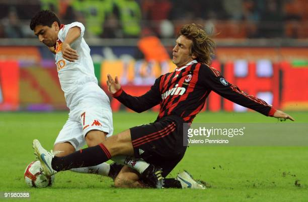 Andrea Pirlo of AC Milan competes for the ball with David Marcelo Cortes Pizarro of AS Roma during the Serie A match between AC Milan and AS Roma at...