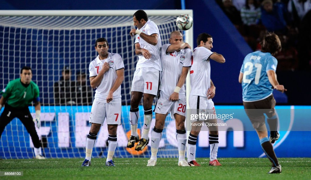 Andrea Pirlo of Italy hits a free kick over the wall defended by Ahmed Fathi Mohamed Shawky Wael Gomaa and Mohamed Aboutrika of Egypt during the FIFA...