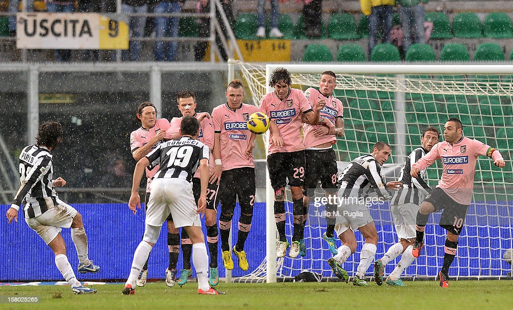 Andrea Pirlo (L) of Juventus takes a free kick from just outside the penalty area during the Serie A match between US Citta di Palermo v Juventus FC at Stadio Renzo Barbera on December 9, 2012 in Palermo, Italy.