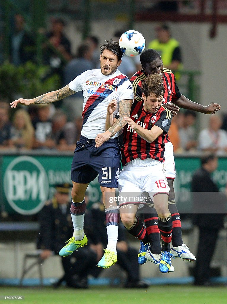 Andrea Poli #16 and Cristian Zapata of AC Milan and Mauricio Pinilla of Cagliari Calcio #51 compete for the ball during the Serie A match between AC Milan and Cagliari Calcio at San Siro Stadium on September 1, 2013 in Milan, Italy.