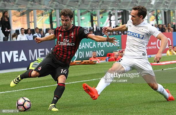 Andrea Poli of AC Milan cis challenged by Sven Kums of Udinese Calcio during the Serie A match between AC Milan and Udinese Calcio at Stadio Giuseppe...