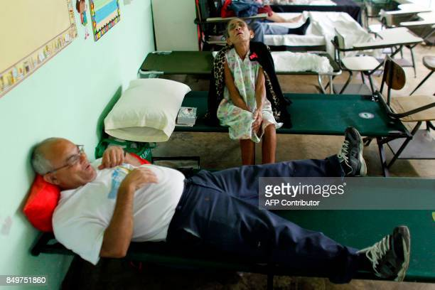 Andrea Rivera and her husband Abigail Acevedo rest at a hurricane shelter as Hurricane Maria approaches Puerto Rico in Fajardo on September 19 2017...