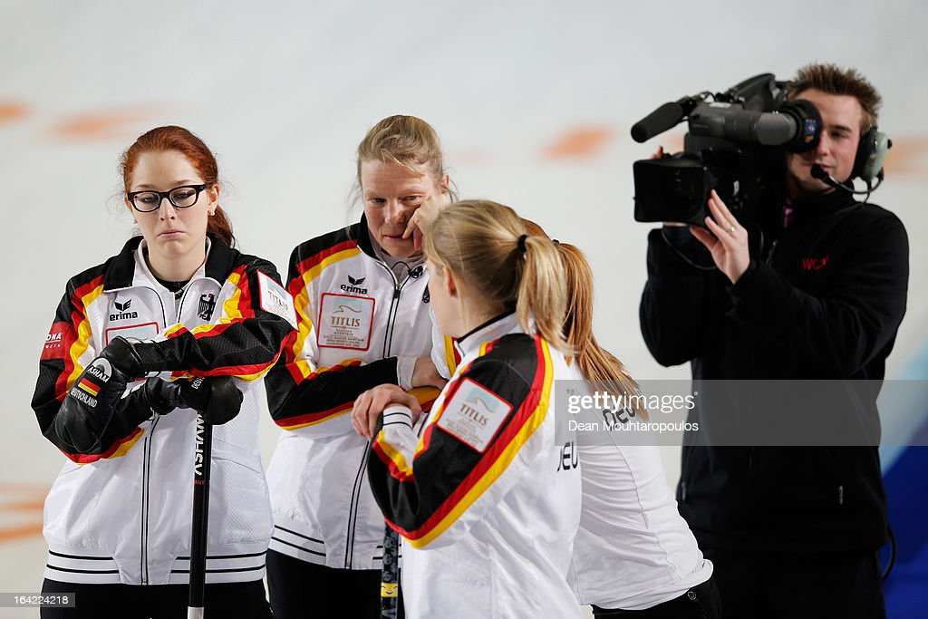Andrea Schopp, Corinna Scholz, Stella Heiss and Imogen Oona Lehmann of Germany wait for a decision in the match between Switzerland and Germany as a TV camera man gets in close on Day 5 of the Titlis Glacier Mountain World Women's Curling Championship at the Volvo Sports Centre on March 20, 2013 in Riga, Latvia.