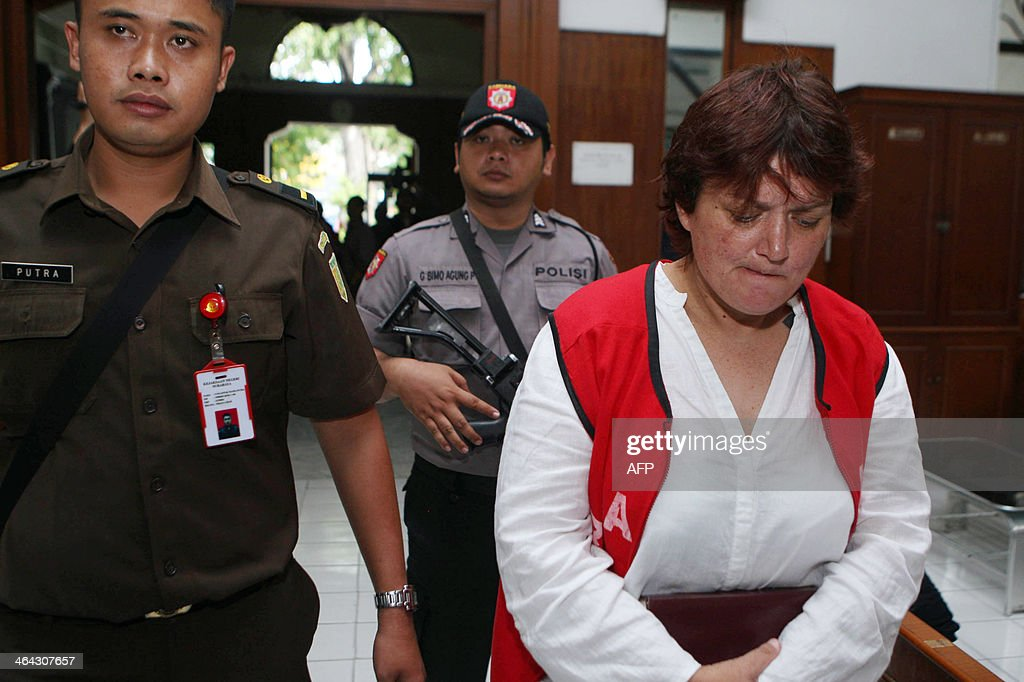 Andrea Waldeck (R) is guarded by officials prior to her trial at a court in Surabaya on January 22, 2014. A British woman was jailed for 14 years on January 22 but escaped the death penalty after admitting that she smuggled crystal methamphetamine into Indonesia from China.