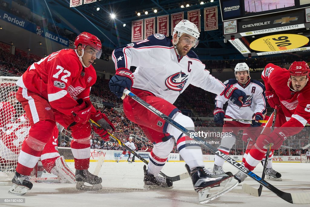 Andreas Athanasiou #72 and Jonathan Ericsson #52 of the Detroit Red Wings battle for the puck with Nick Foligno #71 and Boone Jenner #38 of the Columbus Blue Jackets during an NHL game at Joe Louis Arena on February 7, 2017 in Detroit, Michigan.