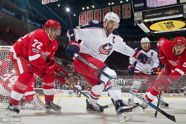 Andreas Athanasiou and Jonathan Ericsson of the Detroit Red Wings battle for the puck with Nick Foligno and Boone Jenner of the Columbus Blue Jackets...
