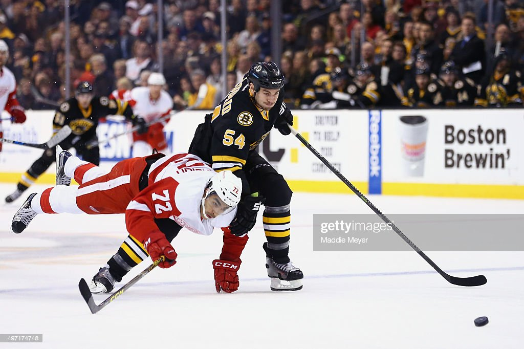 Andreas Athanasiou #72 of the Detroit Red Wings collides with <a gi-track='captionPersonalityLinkClicked' href=/galleries/search?phrase=Adam+McQuaid&family=editorial&specificpeople=2238883 ng-click='$event.stopPropagation()'>Adam McQuaid</a> #54 of the Boston Bruins during the second period at TD Garden on November 14, 2015 in Boston, Massachusetts.