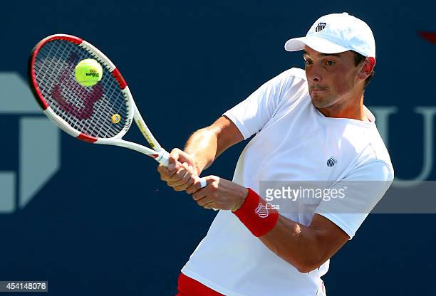 Andreas Beck of Germany returns a shot against Pablo Carreno Bustaon Day One of the 2014 US Open at the USTA Billie Jean King National Tennis Center...