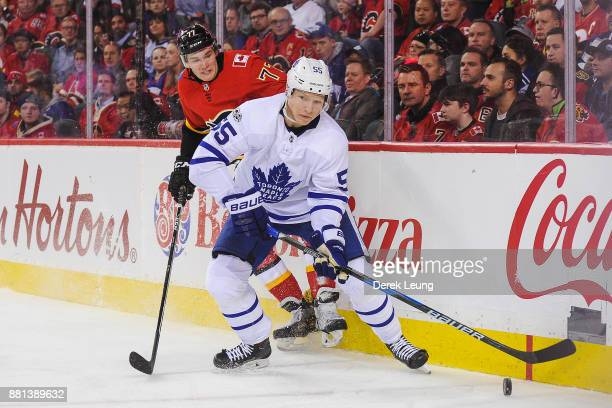 Andreas Borgman of the Toronto Maple Leafs carries the puck past Mark Jankowski of the Calgary Flames during an NHL game at Scotiabank Saddledome on...
