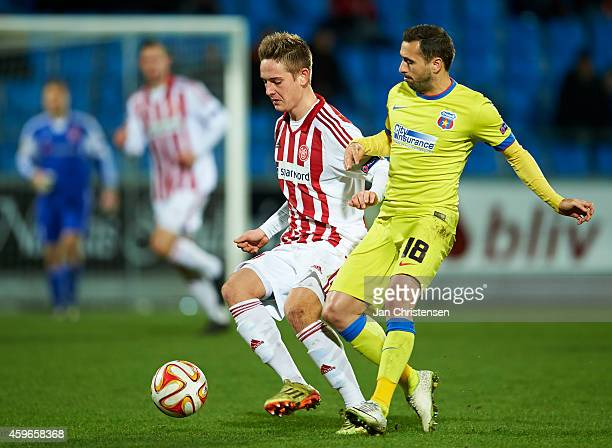 Andreas Bruhn of AaB Aalborg and Lucian Sanmatean of Steaua Bukarest compete for the ball during the UEFA Europa Liga match between AaB Aalborg and...