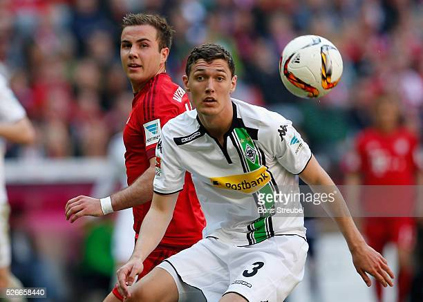 Andreas Christensen of Borussia Moenchengladbach and Mario Goetze of Bayern Muenchen compete for the ball during the Bundesliga match between Bayern...
