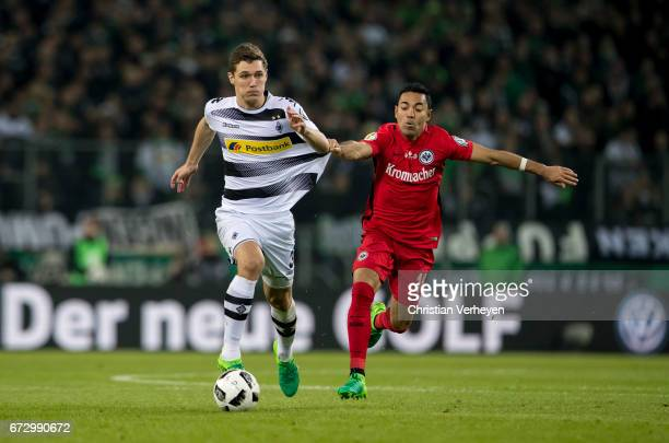 Andreas Christensen of Borussia Moenchengladbach is chased by Marco Fabian of Eintracht Frankfurt during the DFB Cup Semi Final between Borussia...