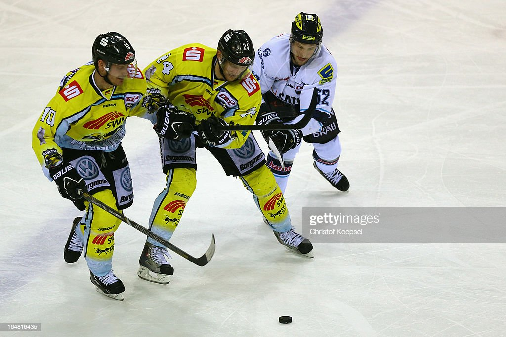 Andreas Driendl of Krefeld Pinguine, Boris Blank of Krefeld Pinguine and Patrick Hager of ERC Ingolstadt struggle for the puck during the fifth DEL Play-Off-match between Krefeld Pinguine and ERC Ingolstadt at Koenigspalast on March 28, 2013 in Wuppertal, Germany.