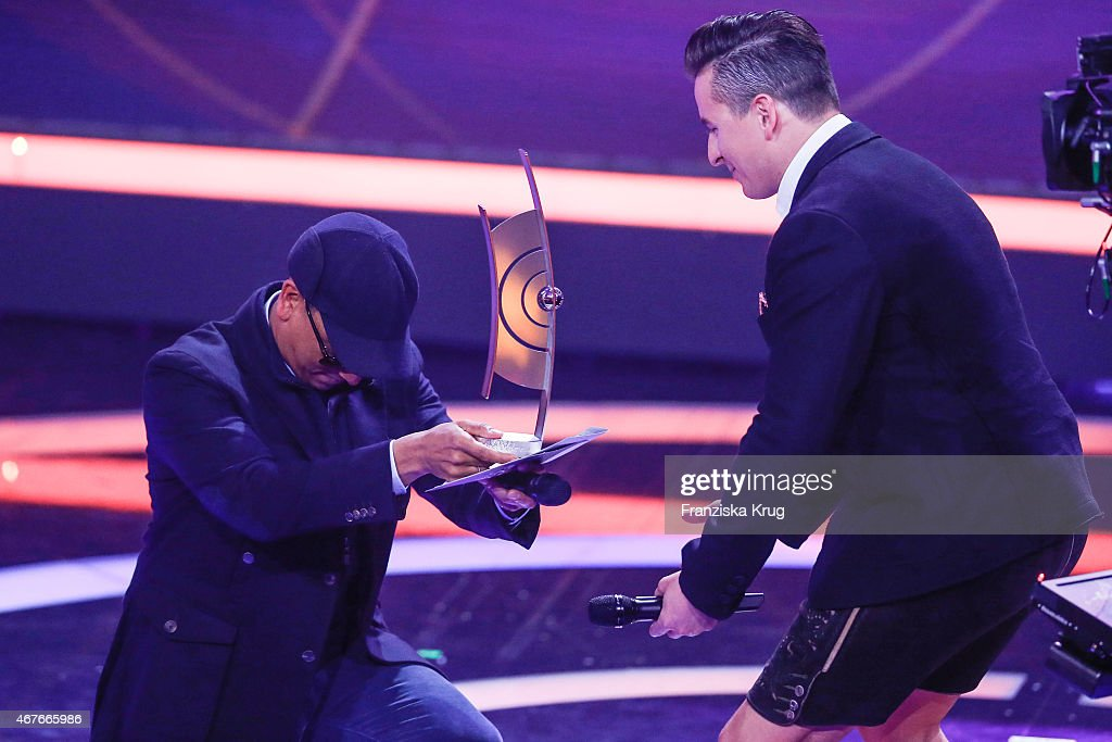 Andreas Gabalier (R) accepts the award in the category 'Volkstuemliche Musik' from Xavier Naidoo at the Echo Award 2015 show on March 26, 2015 in Berlin, Germany.