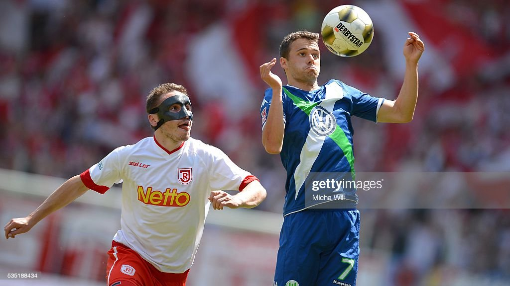 Andreas Geipl (L) of Regensburg and Robert Herrmann of Wolfsburg compete for the ball during the Third League play off second leg match between Jahn Regensburg and VfL Wolfsburg II at Continental Arena on May 29, 2016 in Regensburg, Germany.