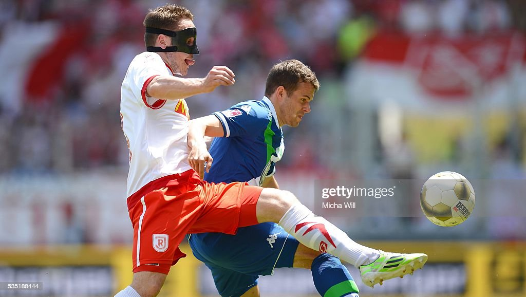 Andreas Geipl (L) of Regensburg and Robert Herrmann of Wolfsburg tussle for the ball during the Third League play off second leg match between Jahn Regensburg and VfL Wolfsburg II at Continental Arena on May 29, 2016 in Regensburg, Germany.