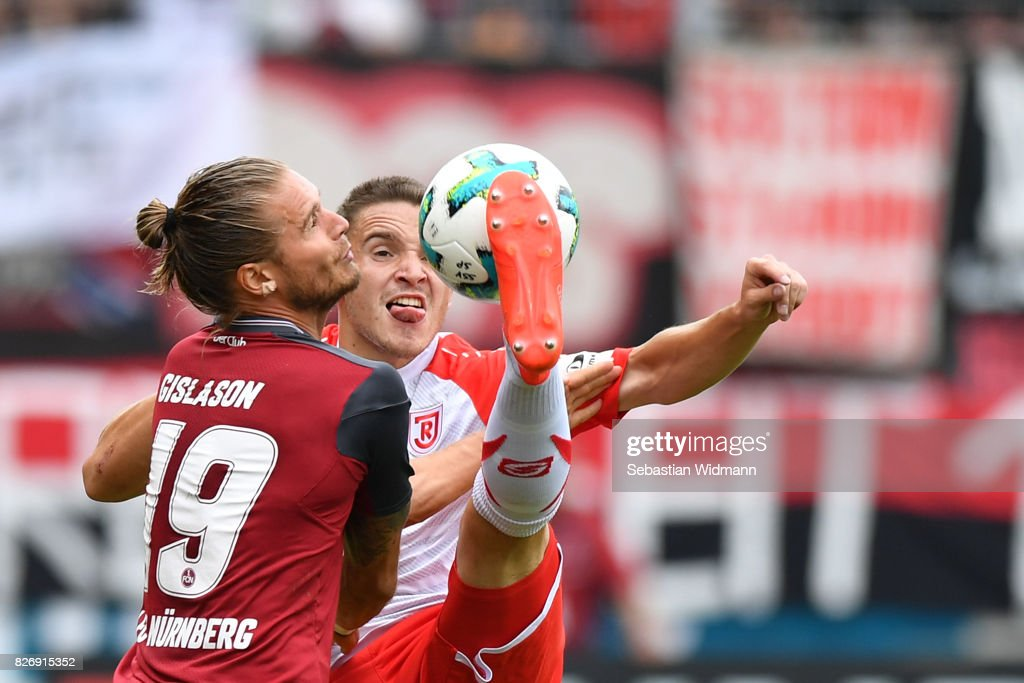 Andreas Geipl of SSV Jahn Regensburg plays the ball while being challenged by Rurik Gislason of 1. FC Nuernberg during the Second Bundesliga match between SSV Jahn Regensburg and 1. FC Nuernberg at Continental Arena on August 6, 2017 in Regensburg, Germany.