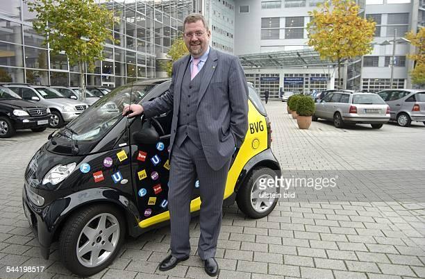 Andreas Graf von Arnim Vorstandsvorsitzender der Berliner Verkehrsbetriebe D vor einem Kleinwagen der Marke Smart mit BVGWerbung im SmartCenter Berlin