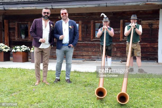 Andreas Haumesser and Joerg Bernicken and Alphorn player during the wedding of Torsten Koch and Annika Hofmann at Wiesergut Alm on July 22 2017 in...