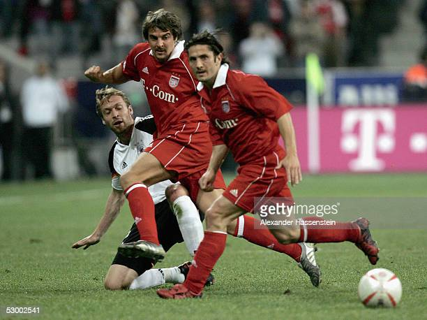 Andreas Hinkel of the German National Team challenge for the ball with Sebastian Deisler and Bixente Lizarazu of Munich during the opening game of...