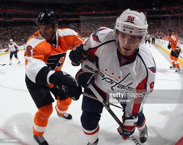 Andreas Lilja of the Philadelphia Flyers checks Marcus Johansson of the Washington Capitals along the boards at the Wells Fargo Center on October 20...