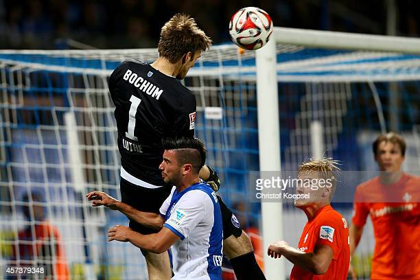 Andreas Luthe of Bochum extends a header against Anthony Losilla and Hanno Behrens of Darmstadt 98 to Mikael Forssell for a late goal during the...